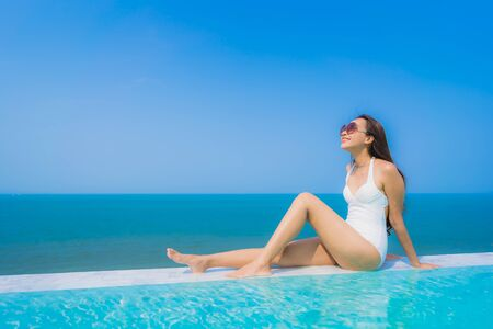 Photo pour Portrait beautiful young asian woman happy smile relax in swimming pool with sea ocean and blue sky for travel vacation and leisure - image libre de droit
