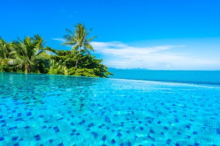 Photo pour Beautiful luxury outdoor swimming pool in hotel resort with sea ocean around coconut palm tree and white cloud on blue sky for holiday vacation travel - image libre de droit