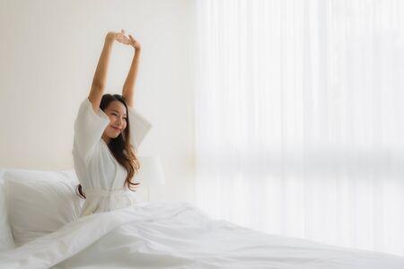 Photo pour Portrait beautiful young asian women smile happy on bed in bedroom interior - image libre de droit