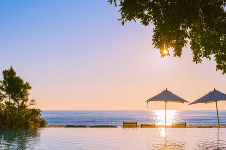 Photo pour Beautiful tropical outdoor beach sea ocean with umbrella and chiar around outdoor swimming pool at sunset or sunrise time for travel vacation - image libre de droit