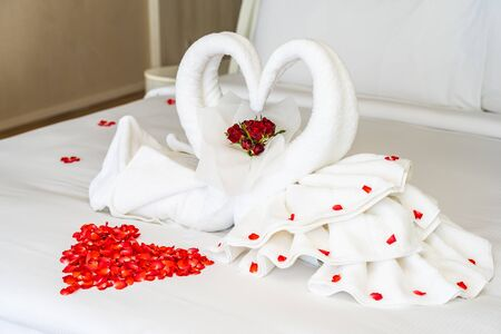 Photo for Swan towel on bed with red rose flower decoration interior of bedroom - Royalty Free Image