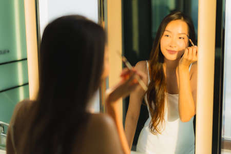 Photo pour Portrait beautiful young asian woman make up with cosmetic powder and lipstick on her face facial in bathroom interior - image libre de droit