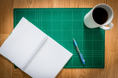 Green Cutting mats  , notebook , pen , cup of coffee on the wood background