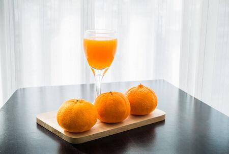 Glass of freshly pressed orange juice with three orange on wooden table