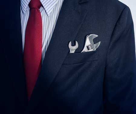 Photo pour Closeup Businessman with spanner in suit pocket - image libre de droit