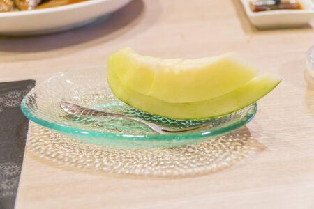 Juicy slice cantaloupe melon on ceramic dish.