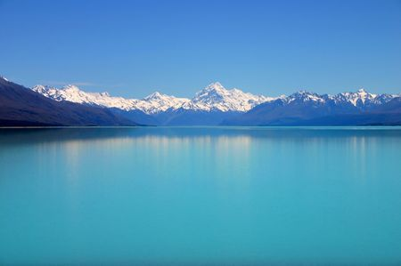 Beautiful mountain turquoise color lake blue sky and snow peaks reflecting in the water. Un