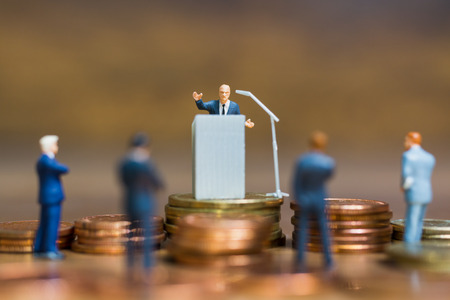 Miniature people : Businessman speaking on the podium , Business and finance investment concept