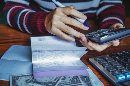 Photo pour Women is using a calculator to calculate the amount of her deposits. - image libre de droit