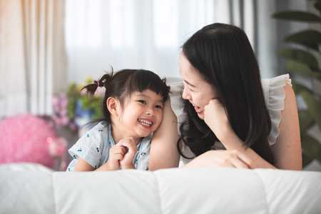 Foto de Happy asian family mother with daughter playing on bed with smile face. - Imagen libre de derechos