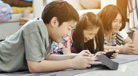 Foto per Children playing tablet or smartphone at home , Asian boy and girl playing game on mobile phone together with smile face. - Immagine Royalty Free
