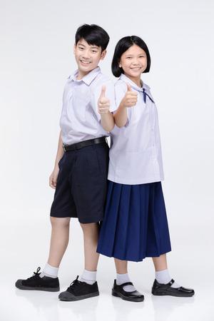 Photo pour Portrait of cute asian girl and boy in student's uniform on gray background. Back to school concept . - image libre de droit