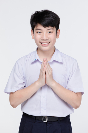 Photo pour Asian child boy in student's uniform, acting sawaddee mean Hello . on gray background - image libre de droit