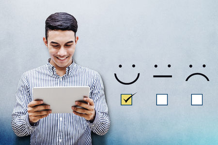 Photo pour Customer Experience Concept, Happy Businessman holding digital Tablet with a checked box on Excellent Smiley Face Rating for a Satisfaction Survey - image libre de droit