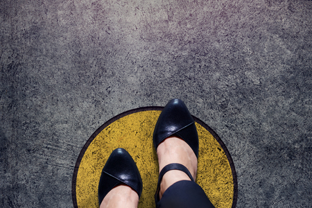 Photo for Comfort Zone concept, Woman with leather shoes Steps over circle line to outside bound, Top view and Dark tone, Grunge Dirty Concrete Floor as Background - Royalty Free Image
