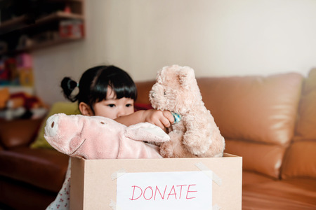 Child with Donation Concept. 2 Years Old Child putting her old Dolls into a Donate Box