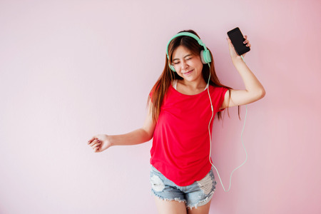 Photo pour Young Woman Enjoying with Music From Smart Phone in House, Listening and Dancing in Happy Moment - image libre de droit