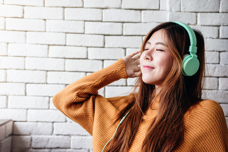 Foto de Young Woman Listening Music From Headphone in Cozy House, Closed Eyes and Relaxing in Happiness moment - Imagen libre de derechos