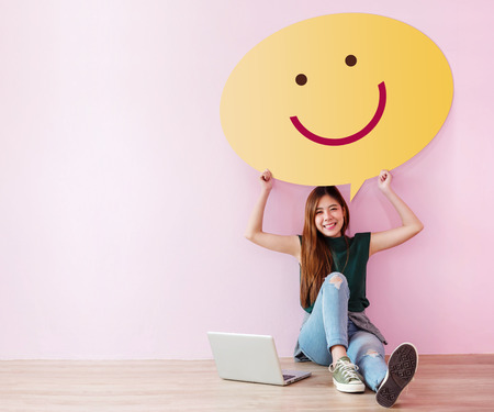 Photo pour Happy Customer Concept. Review and Feedback her Experience for Satisfaction Survey Online. Young Female in Cheerful Posture, Raise up Speech Bubble with Smiley Face. Sit on the Floor with Laptop - image libre de droit