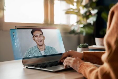 Photo for Working From Home Concept. Online Meeting for Small Business Partnership. Young Employee Woman making a Video Call to Talking a Business Topic with her Smiling Man Partner via Computer Laptop. Side View - Royalty Free Image