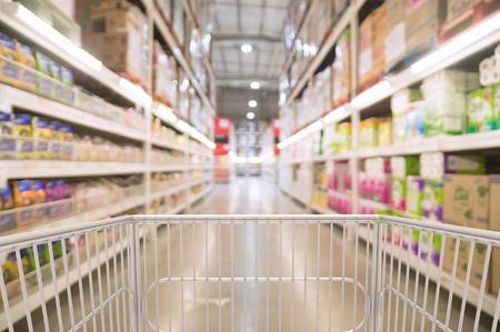 Foto de Trolley Shopping Cart Between Dry Grocery Shelf Section in Supermarket or Hypermarket Warehouse Retail Outlet as Modern Lifestyle Shopping Concept with bokeh. - Imagen libre de derechos