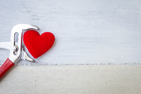 Red heart in metal pliers over white wood background