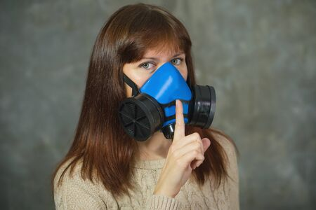Photo pour Young woman in respirator shows sign of silence on grey background. Virus protection concept. - image libre de droit