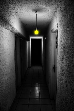 Yellow light glowing in dark underground corridor.