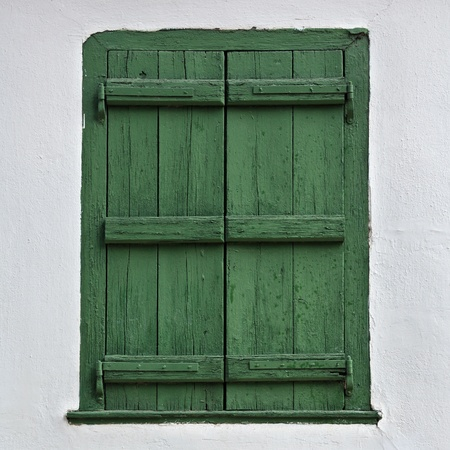 Green wooden window shutter and white wall.
