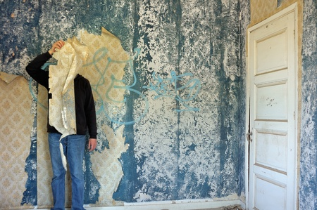 Male figure behind torn wallpaper shred in abandoned building interior.
