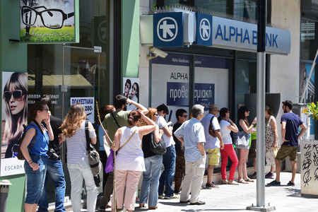 ATHENS, GREECE - JULY 1, 2015: Long line of people waiting to withdraw cash money from ATM cashpoint outside a closed bank. Capital controls during greek financial crisis.