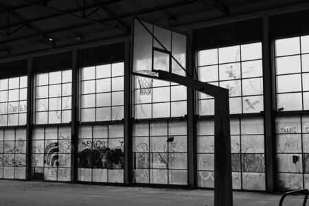 Abandoned basketball court gym interior and glass wall broken windows. Black and white.