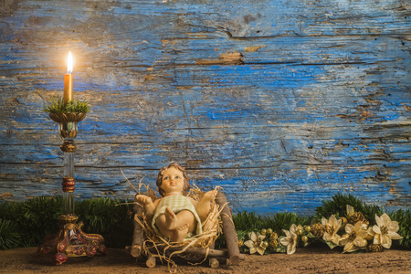 Photo for Christmas card, baby Jesus in his crib and vintage candle in rustic wooden background with copy space - Royalty Free Image
