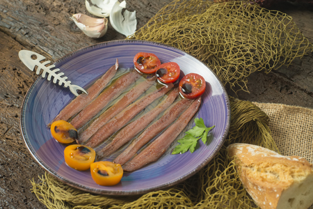 Foto de Plate of salted anchovies with olive oil, tomatoes and garlic on an old wooden table, still life. - Imagen libre de derechos