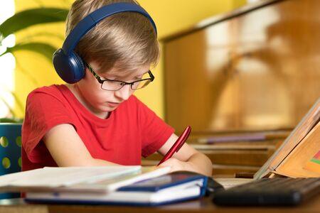 Photo pour blond boy does homework at the table in headphones - image libre de droit