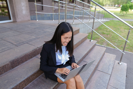 Modern young women, business people, international students holds laptop and study work plan, solve important problems and smiling sits on stairs on background of gray wall of business center outdoors. Woman with black hair, dressed in white blouse and cl