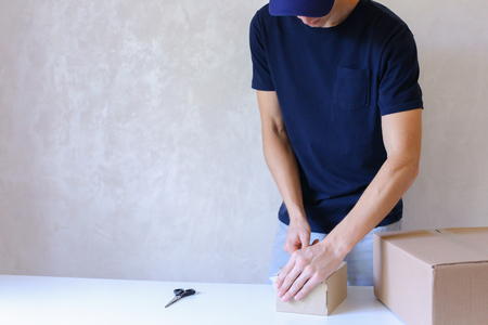 Deliveryman Standing in Room, Glue Tape Box and Takes Parcel in Hands and Smiling . Postman European Appearance in a Black T-Shirt and Cap Stands Near the Desk in the Office With White Walls and Unassisted Packaging Boxes, Adhesive Glue Tape on a Cardboar
