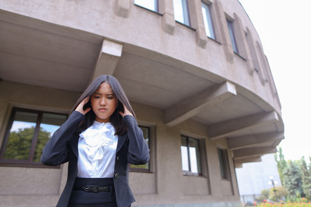 Pretty young perspective business woman, student holds on head from fatigue, rests, took break from work and stands on background of abstract  business center on street in open air. Woman with black hair, dressed in white blouse and classic jacket with bl