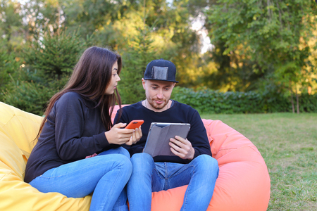 Pair of lovers of young attractive people sitting in soft yellow and red chair, man uses gadget that keeps in arms, female holds plastic card, coupon. Young people cute communicate, plan to travel, choosing interior of apartment, she shows on flyer and gu