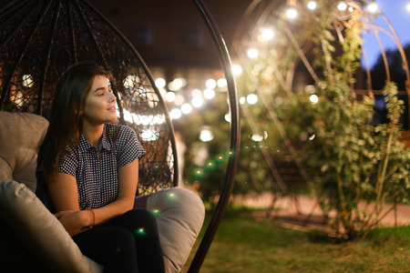 Beautiful young and modern woman resting outside in restaurants and sitting in chair suspended on background of glowing lights. Girl dreamily lost in thought and expects evening gatherings with friend outdoors summer warm evening.Concept of beautiful succ