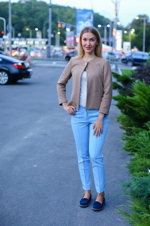 Women with blond hair european appearance smiles and removed advertising for clothes and accessories, womens magazine or waiting for friend. Girl dressed in bright light blouse, beige jacket, blue trousers and dark blue ballet flats. Concept of stylish gi