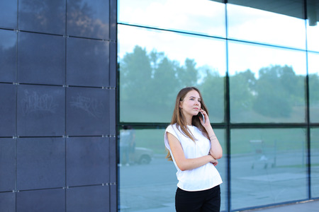 Young beautiful business woman entrepreneur with long hair wearing a suit standing near center business technology. Female work, negotiating, solves problems, dials, talking on smart phone