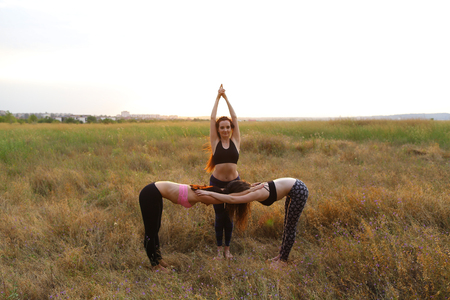 Girls perform postures or asanas of yoga, posing for photographer to take advertising pictures for sports womens clothing catalog, meditate outdoors in wide field. Girl with shoulder-length hair dressed in pink top and black leggings, girl with long red h