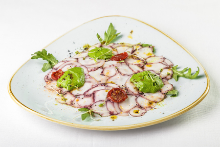Thin slices of octopus with green sauce garnished with sprigs of dried tomato and arugula on triangular plate with smooth edges blue with gold edging on white background. Concept is delicious and beautiful food, restaurant supply of snacks and main dishes