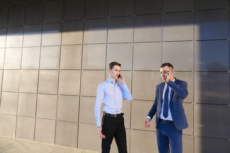 Two goodly active confident young male men, businessman, students talking on phone, solve important questions, make plans, arranging meetings and stand on background wall of modern business center outdoors. One of guys dressed in blue classic suit, white