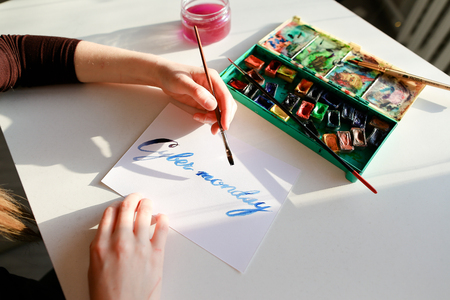 Creative woman holds thin wooden brush in hands and writes in beautifully italic typeface text from letters Cyber Monday on white sheet of paper in blue colors, sitting at white table on which there watercolor and glass jar with water in art studio. Europ