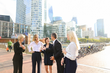 Financial team employees speaking with boss in La Defense Paris. Concept of decision making and business meeting. Responsible people planning work outside.