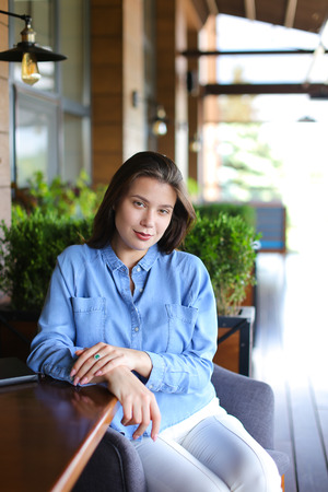 Young woman sitting at cafe in room plants background and wearing jeans shirt. Concept of having break and resting.