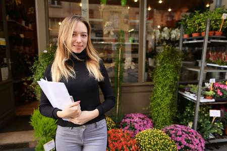 Beautiful female manager of flower shop standing with papers. Concept of floral business and room plants.