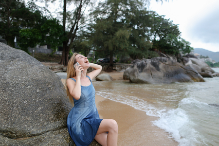 Young pretty girl sitting on sand near sea and stones, speaking by smartphone. Concept of modern technology and resting on beach in morning.
